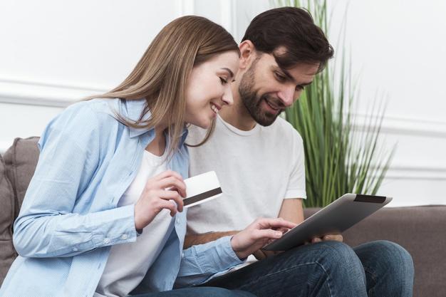 Como identificar um bom pagador. Um casal fazendo compras online por meio de um tablet e sorrindo.